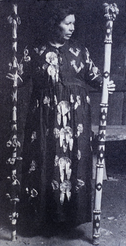 woman in long dress adorned with abalone shells holding decorated wooden staffs